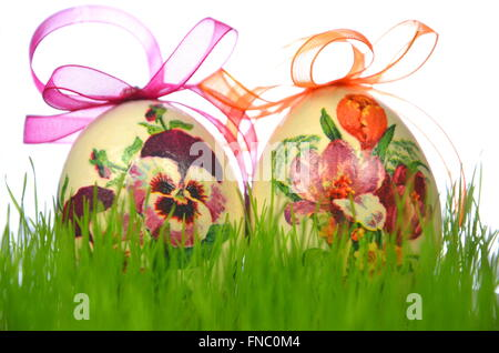 Easter eggs decorated with flowers made by decoupage technique in the grass - Stock Photo