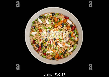 Mixed dried legumes and cereals in white bowl on black background. Top view - Stock Photo