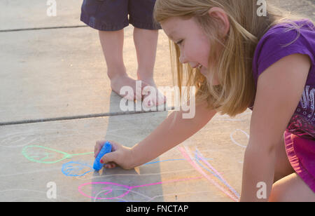 A young girl drawing with chalk on a light colored driveway while her younger brother watches. - Stock Photo
