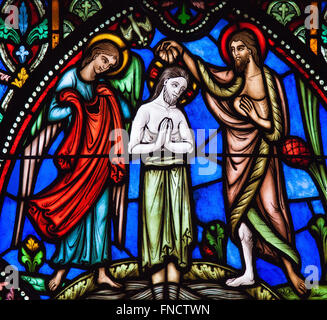 Stained Glass window of Jesus' baptism in the river Jordan by Saint John the Baptist, in the Cathedral of Brussels, - Stock Photo