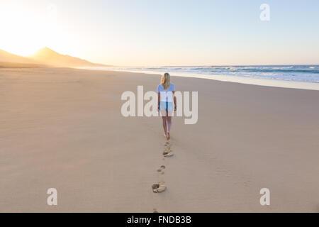 Lady walking on sandy beach in sunset. - Stock Photo