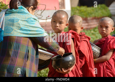 Young monks on their morning alms rounds, Bagan, Myanmar - Stock Photo