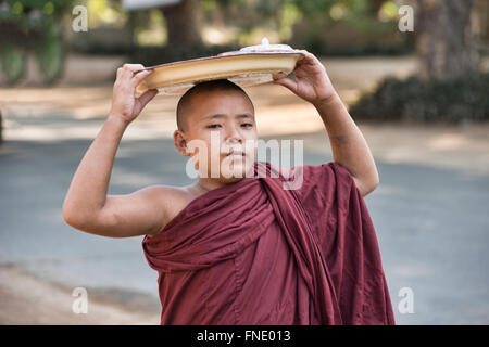 A young monk on his morning alms round, Bagan, Myanmar - Stock Photo
