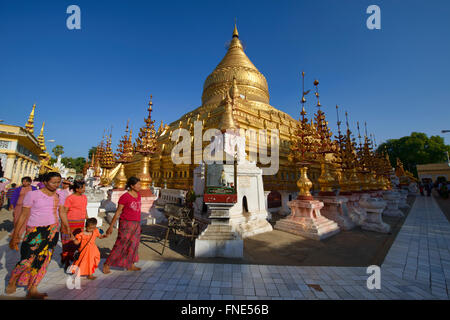 Pilgrims walking at golden Shwezigon Pagoda, Bagan, Myanmar - Stock Photo