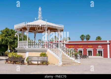 The kiosko or gazebo in San Jose del Cabo's main square in Old Town, with benches beside and colorful red restaurant - Stock Photo
