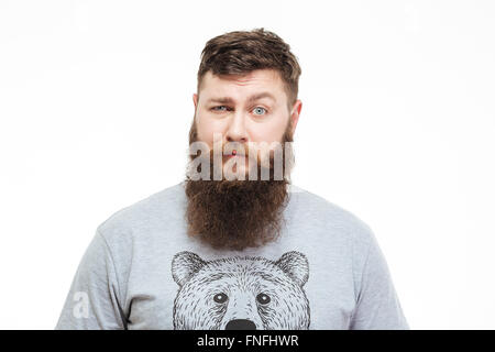 Portrait of confused handsome man with beard looking at camera over white background - Stock Photo