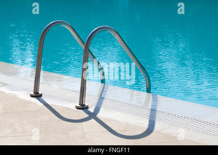 Metal stairs leading into a swimmingpool - Stock Photo