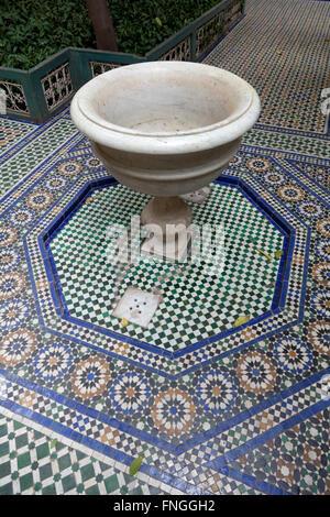 Traditional mosaic floor and marble fountain in Palais de la Bahia, Marrakesh, Morocco - Stock Photo