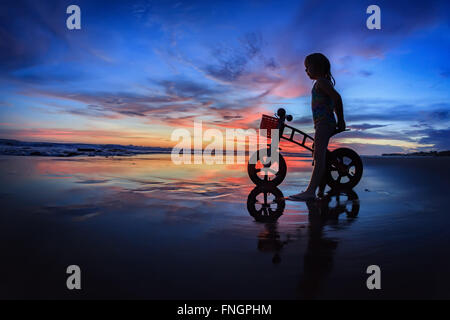 Black silhouette of little child - run bike rider stand on wet sand beach, look at sea surf and colourful sunset - Stock Photo