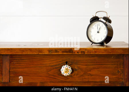 Retro alarm clock on bedside table,  background white wooden wall - Stock Photo