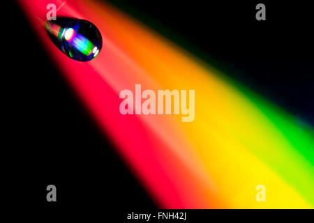 Water drop on dvd disk. Multi colored background, like a rainbow - Stock Photo