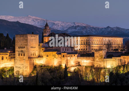 View at dusk of Alhambra palace with the snowy Sierra Nevada in the background, Granada, Andalusia, Spain - Stock Photo