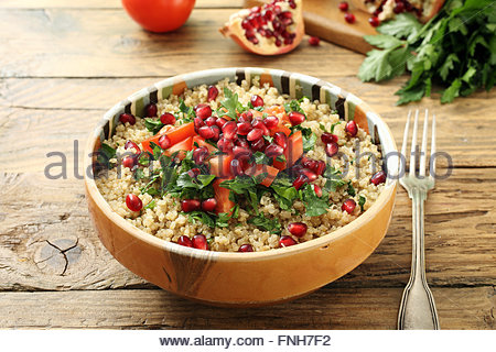 closeup quinoa salad with pomegranate herbs and tomatoes on rustic kitchen table - Stock Photo