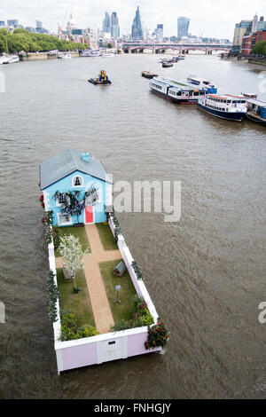 A single family house floating down the river thames in central London - Stock Photo