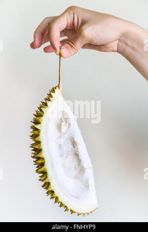 a piece of durian peel held by the stem by the hand of a young woman fnhyp9