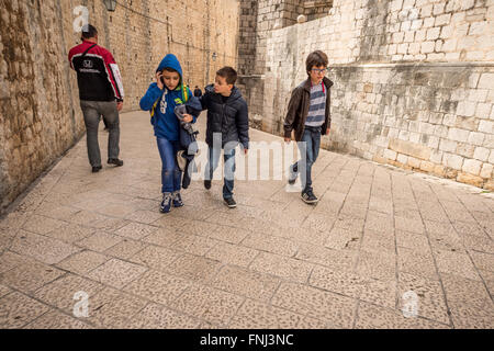 Children walking home after school in the old city of Dubrovnik, Croatia. - Stock Photo
