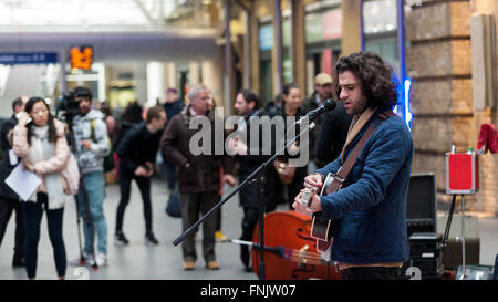 London, UK.  16 March 2016. Guitarist, King Charles performs.  Buskers and street performers entertain commuters - Stock Photo