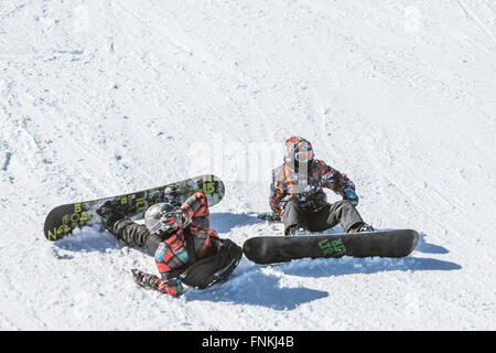Sofia, Bulgaria - March 12, 2016: Two teenage snowboarders are sitting on the ski slope just before a freestyle - Stock Photo
