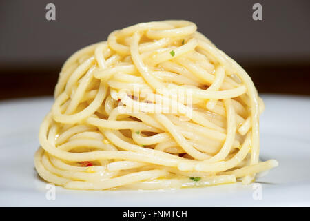 spaghetti with garlic, oil and hot peppers with parsley and fork on table - Stock Photo