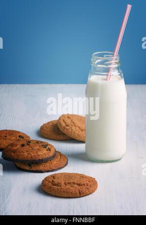 Chocolate chip cookies with a milk bottle with a straw on a white wooden table and blue background. - Stock Photo