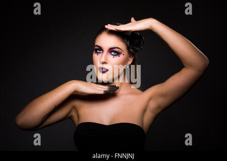 Blond woman wearing gothic make-up with black painted fingertips striking a vogue pose - Stock Photo