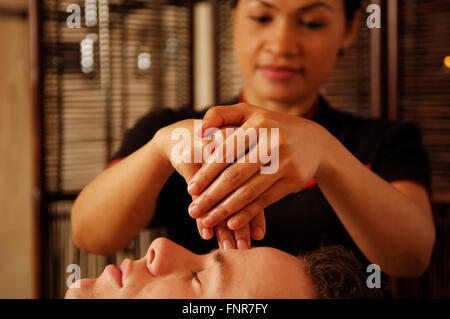 A Thai masseuse giving a young man a craniosacral full head massage to manipulate the bones of his skull, face and - Stock Photo