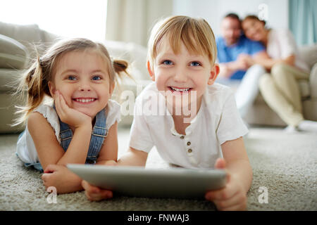 Happy children using touchpad with parents in the background at home - Stock Photo