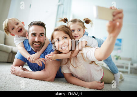 Happy young family taking selfie on the floor at home - Stock Photo