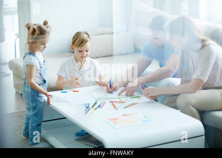 Children drawing at the table with their parents - Stock Photo