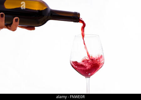 Wine poured from a bottle in a wine glass, on a white background - Stock Photo