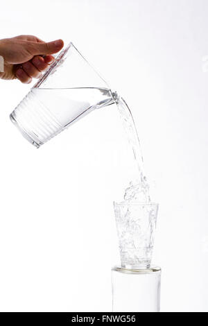 Water, vigorously poured from a jug overflowing splashing from a glass, on a white background - Stock Photo