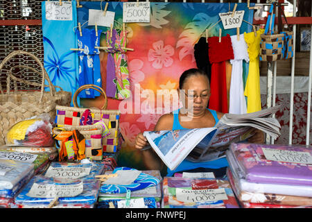 Woman selling colorful pareu wraps being sold at a market in Papeete on the island of Tahiti, French Polynesia, - Stock Photo