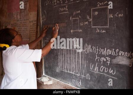 A teacher writes on the blackboard in her classroom in Finote Selam Ethiopia Africa - Stock Photo
