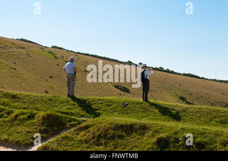 A couple of middle-aged hikers admiring and photographing the view from Windover Hill on the South Downs Way near - Stock Photo