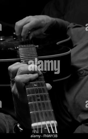 Practicing steel string guitar at home- focus on left hand - Stock Photo