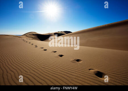 Bright sun over footsteps in remote desert sand dunes, Great Sand Dunes National Park, Colorado, USA. - Stock Photo