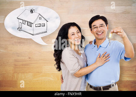 Composite image of smiling couple holding a set of keys - Stock Photo