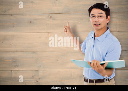 Composite image of elderly man pointing behind him - Stock Photo