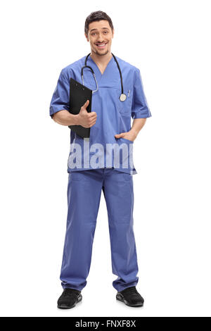 Full length portrait of a young male healthcare professional holding a clipboard and looking at the camera - Stock Photo