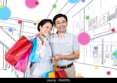 Composite image of older asian couple with shopping bags - Stock Photo