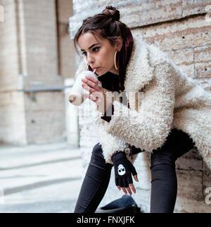 young pretty stylish teenage girl outside on city street fancy fashion dressed drinking milk shake - Stock Photo