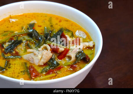 Tom yum soup with chicken on wooden table - Stock Photo
