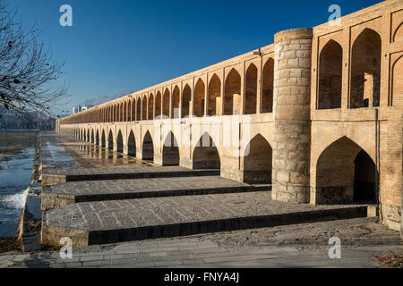 Early morning view of Allahverdi Khan Bridge (Se-o-se Pol, 33 Arches Bridge) over the Zayandeh River, Isfahan, Iran. - Stock Photo