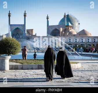 Chador clad women at Imam Square with fountains and the dome and minarets of Imam Mosque in background. Isfahan, - Stock Photo