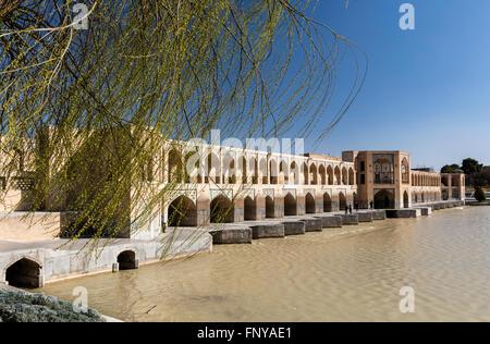 Budding willow framing springtime view of Khaju Bridge, Zayandeh River, Isfahan, Iran - Stock Photo