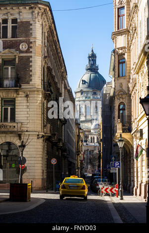 Budapest, Hungary - March 14, 2016: Yellow taxi driving toward St. Stephen's Basilica on Lazar street in Budapest, - Stock Photo