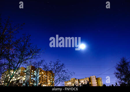 The starry sky and the moon over the buildings. View from my window. Moon and star dust in the sky. - Stock Photo