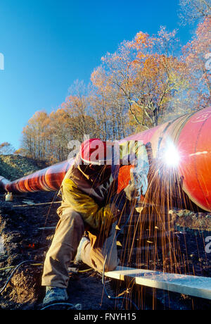 Man welding a pipeline seam in rural West Virginia; USA - Stock Photo