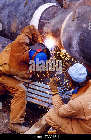 Man welding a gas pipeline seam for installation under the Delaware River; rural Pennsylvania; USA - Stock Photo
