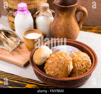 Gourmet freshly baked crusty cheese rolls with fresh milk in pottery containers for a healthy farm breakfast - Stock Photo